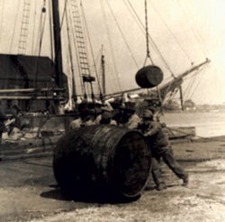 archival image of men rolling a cask